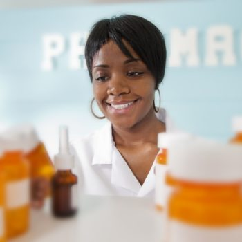 Pharmacist works in a pharmacy.  She reviews shelves filled with prescriptions, medication dosage and drug interactions at a local pharmacy.   View of one African descent female pharmacist through shelves.